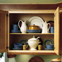 Cabinet opened to show dishware and serving pieces stored inside